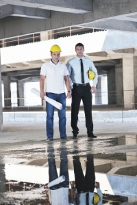 Building Surveyor and Project Manager on Building Site Discussing Problem