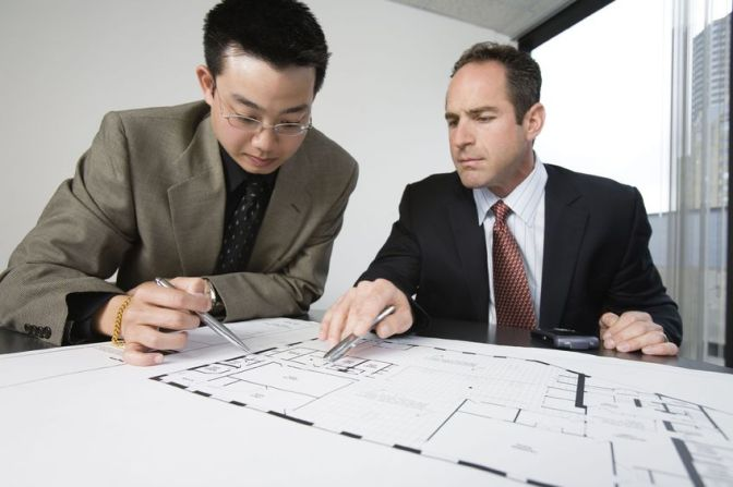 Two architects discussing on blueprints in an office